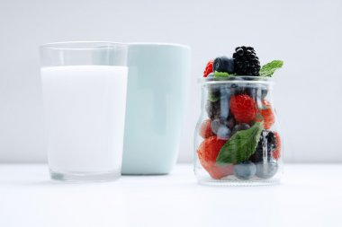 Jar with berries and mint located on white table