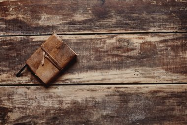 paper notebook with leather cover on a wooden table