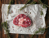Top view meat steak with bone on craft paper; salted
