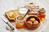 Side view of breakfast set with jam, bread, butter, walnuts