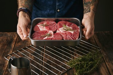 tattooed hands offers steaks in pan for camera