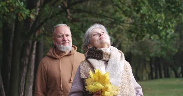 Starší pár na procházce v lesoparku, podzimní den, šedovlasý muž přijde ke své ženě a zakryje jí oči rukama, podzimní nálada.