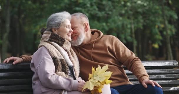 Dospělý pár sedí na lavičce v lesoparku, mluví a směje se, šedovlasý muž a žena komunikují v přírodě, starší generace, podzimní nálada.