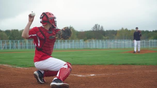 Főiskolai baseball, a dobó dobja a labdát felé elkapó, elkapó sikeresen elkapja a gyors labdát, a srácok edzés baseball, vissza nézet.