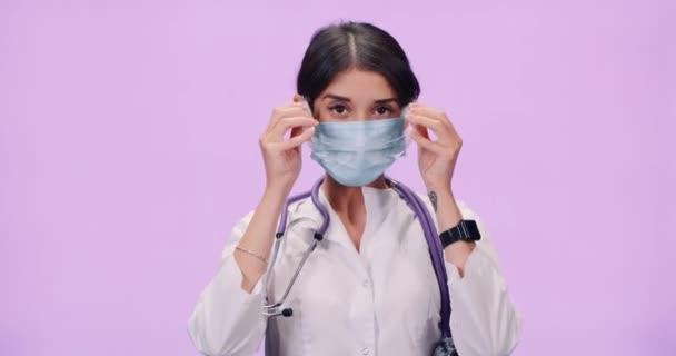 Porträt einer jungen Ärztin in Schutzkleidung und medizinischer Maske, Frau setzt Schutzbrille auf und blickt in die Kamera, Schutz vor einem Virus, rosa Hintergrund.