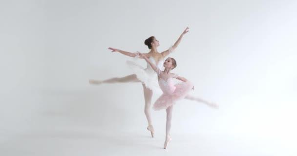 Eine Frau und ein kleines Mädchen im weißen Tutu tanzen Ballett und führen choreografische Elemente auf weißem Hintergrund auf, Probe.