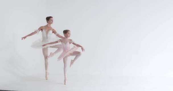 Young female and little girl in a white tutu, dance ballet and perform choreographic elements on a white background, rehearsal.