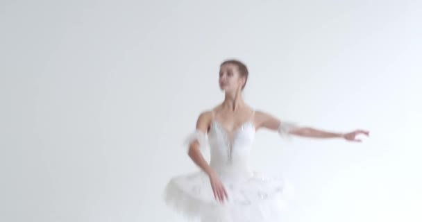 Elegant female in a white tutu, dance ballet and perform choreographic elements on a white background, rehearsal.