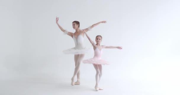 Junge Frau und kleines Mädchen im weißen Tutu, tanzen Ballett und führen choreografische Elemente auf weißem Hintergrund auf, Probe.
