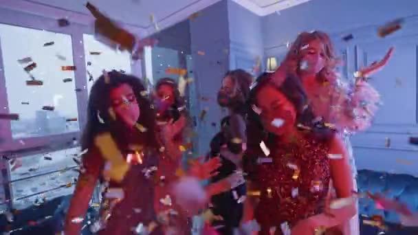 Luxus-Party, schöne Glamour-Frauen mit Schutzmasken tanzen im Nachtclub, goldenes Konfetti fliegt durch die Luft, Neonlicht, private Party während der Pandemie, 4k Zeitlupe.