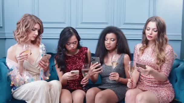 Glamorous females sitting in the lounge area in night club, use their smartphones and hold champagne glasses in their hands, online communication.
