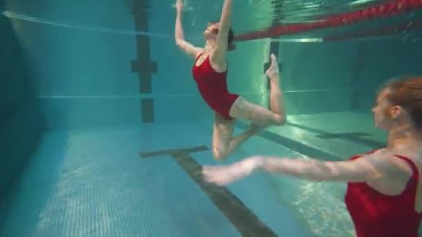 Profesionální plavci v bazénu, mladá žena provádí prvky synchronizovaného plavání, krásný tanec pod vodou, synchronizovaný plavecký trénink.
