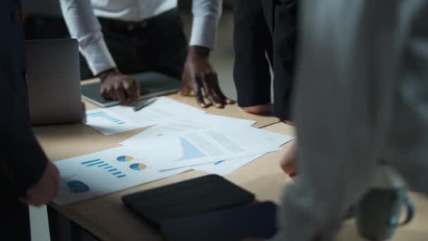 Obchodní jednání, mezinárodní management tým v práci, tým stojí vedle pracovního stolu a pracuje s dokumenty, diskutovat o pracovních plánech a plánování finanční statistiky, brainstorm, pohled na