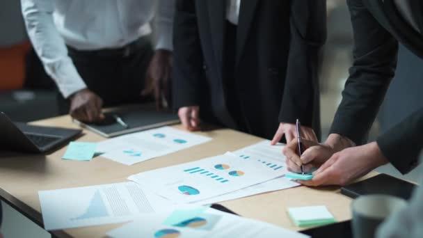 mezinárodní management tým v práci, tým stojí vedle pracovního stolu a pracuje s dokumenty, podnikatelé spojují ruce.