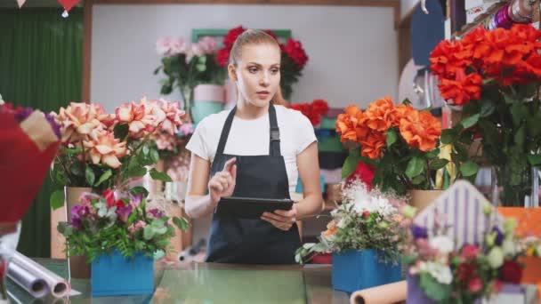 Květinářství žena dělá inventář v květinářství, žena používá sítotisk tabletu spočítat počet květin a rostlin v květinářství.