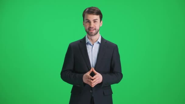 Man reporter in suit looks into the camera and speaks, stands on a green background, a template for TV news agencies, journalist at work, chromakey.