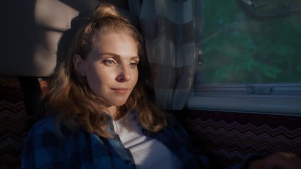 Young woman freelancer working at a laptop while sitting in a car, typing text and remote work in nature, portrait in a sunset light inside a camping car, slow motion.
