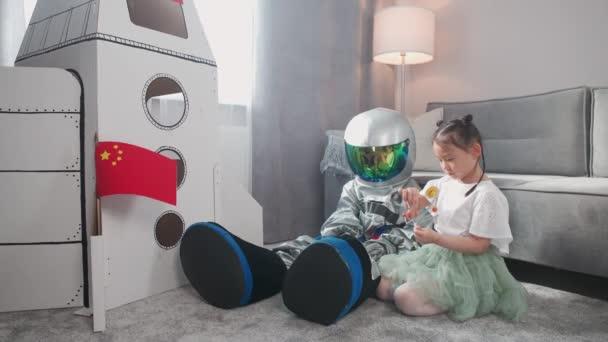 Asijské děti hrají v obývacím pokoji doma, chlapec v kostýmu astronauta sedí na podlaze se svou sestrou, děti si hrají s hračkou model sluneční soustavy, 4k zpomalený film.