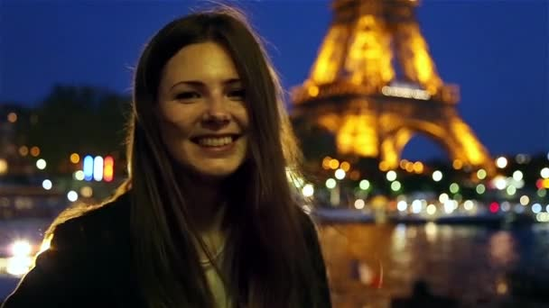 Happy girl smiling in the evening at the Eiffel tower in Paris