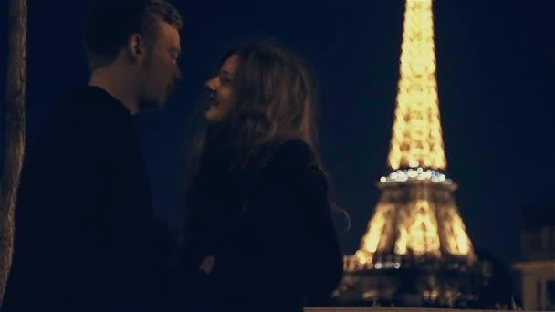Milenci mluví v noční době v Paříži na Eiffelovu věž