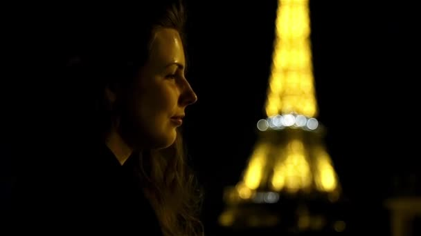 Dreaming girl at night time in Paris at the Eiffel tower
