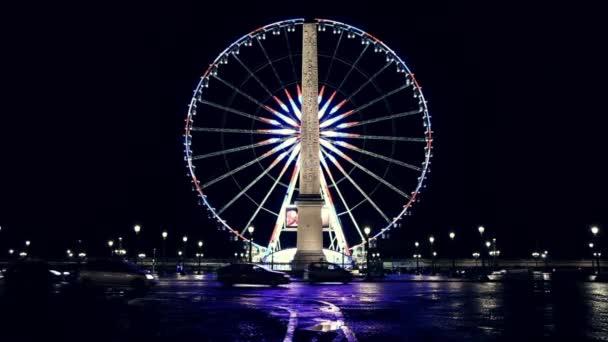 Osvětlené roue de Paris a Obelisk Louxor v noci v Paříži