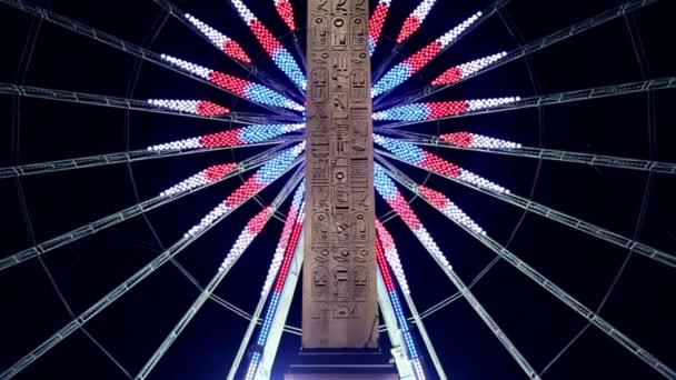 Roue de Paris za obeliskem Louxor v noci v Paříži