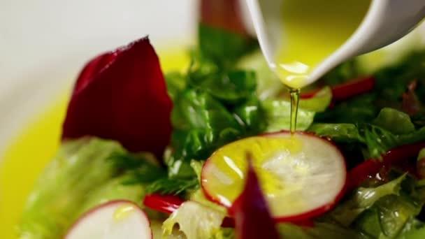 Zeleninový salát a olivový olej v pomalém pohybu