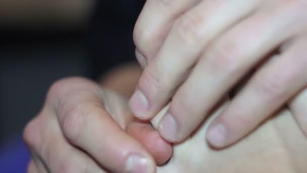 Muž masíruje žena nohy