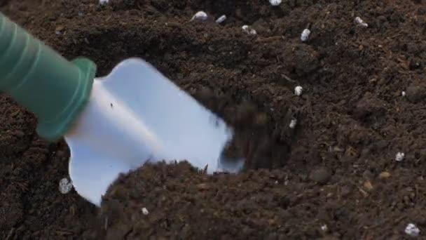 Míchání nečistoty s hnojivem s rukou lopatu