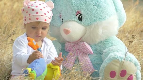 malá dívka si hraje s hračkami v přírodě