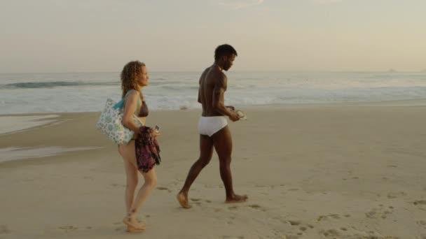couple walks along Ipanema beach