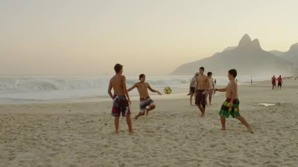 Boys kicking a football at the beach