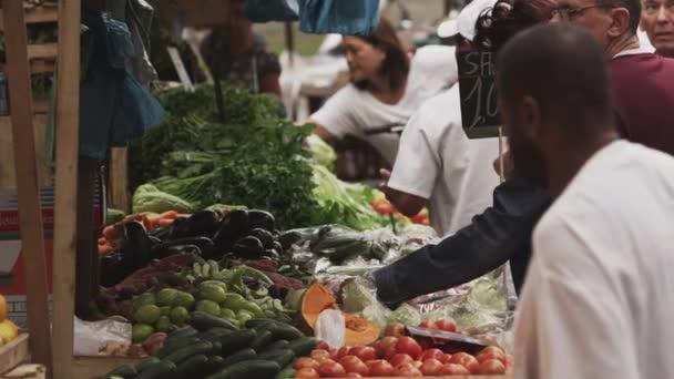 lidé nakupující produkty na trhu v Riu