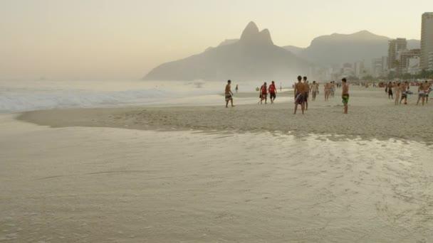 Teens kick a football at Ipanema beach