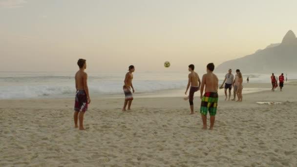 Hoši kopající fotbal na pláži