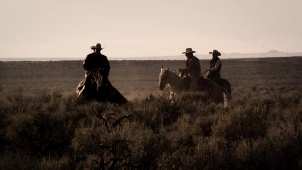 cowboys riding at dusk through brush.