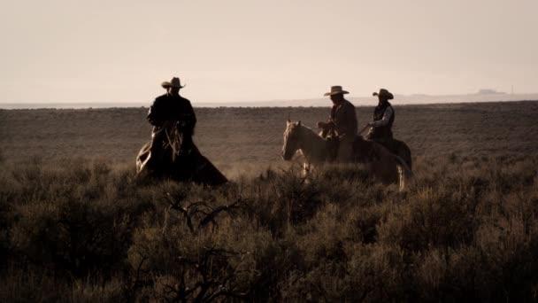 kovbojové jedoucí za soumraku přes kartáč.
