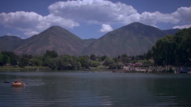 zwei Personen paddeln mit einem Floß auf einem See.