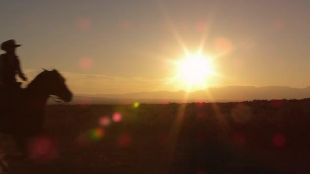 kovbojové při západu slunce.