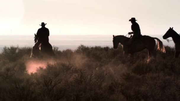 kovbojové cválání pouští.
