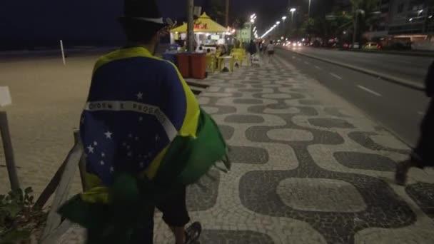 Muž, zahalený do brazilské vlajky