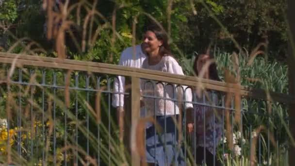 Zpomalený záběr rodiny na mostě v krásné zahradě