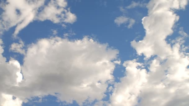 Time-lapse of fluffy clouds in a bright blue sky.
