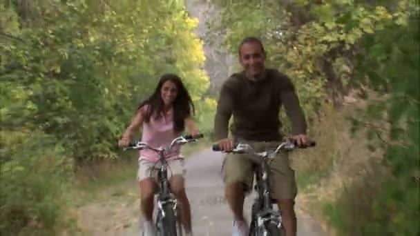 Muž a žena na kolech dolů stromy porostlém cestu