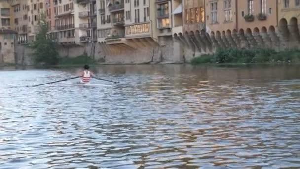 Mann paddelt mit einem kleinen Boot auf einem Fluss in Italien.
