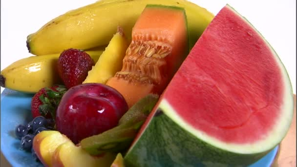 Assortment of fruit rotating on a white screen.