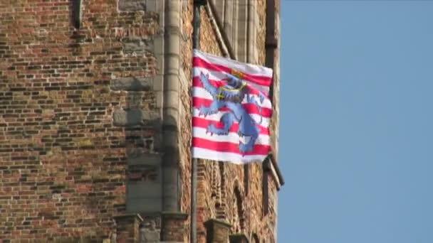 Bruges, Belgium heraldic flag flying on a pole at a building corner.