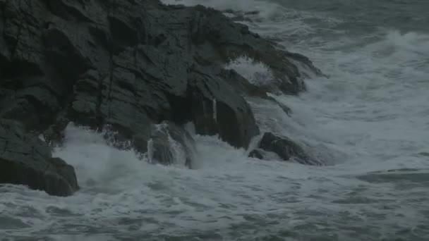 Nahaufnahme der Wellen auf einem Felsvorsprung in Maine.