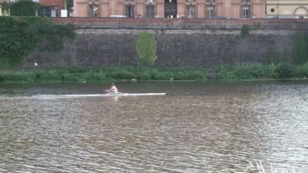 Mann paddelt auf einem Fluss in einer italienischen Stadt.